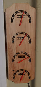 A wooden board hanging upright on a wall. Four semi-circle indicator dials are spread across its length, with red needles pointing to numbers.